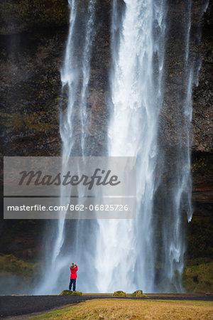 Europe, Iceland, tourist at Seljalandsfoss waterfall (MR)