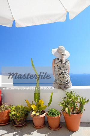Woman on steps in town of Oia, Santorini, Kyclades, South Eagean, Greece,Europe  Model release 0009