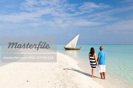 Maldives, Rasdhoo Atoll, Kuramathi Island. A couple on honeymoon stand looking at a traditional Maldivian Dhow on the sandbank at Kuramathi Island Resort. MR.