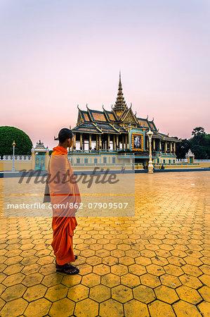 Cambodia, Phnom Penh. Buddhist monk looking at silver pagoda, royal palace complex , at sunset (MR)