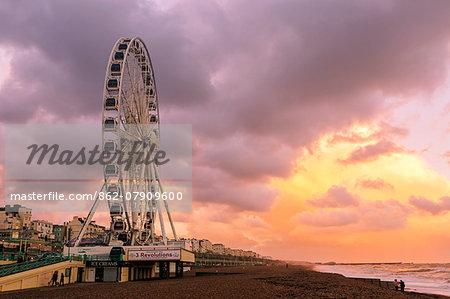 Europe, United Kingdom, England, East Sussex, Brighton and Hove, Brighton, the Brighton Wheel and Brighton beach at sunset