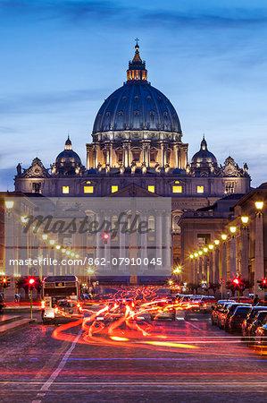View of the Basilica of St. Peter's and St. Peters Squaredown the Via Della Conciliazione, with traffic  at twilight, Borgo, Rome, Lazio, Italy.