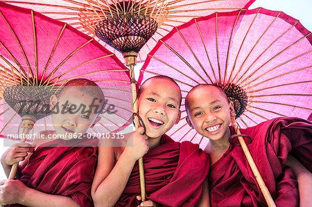 Myanmar, Mandalay division, Bagan. Portrait of three novice monks under red umbrellas (MR)