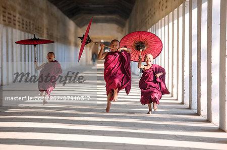 Myanmar, Mandalay division, Bagan. Three novice monks running with red umbrellas in a walkway (MR)