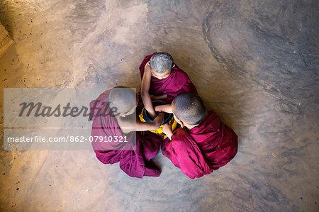 Myanmar, Mandalay division, Bagan. Three novice monks with alms bowl, inside a pagoda (MR)