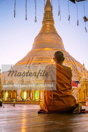 Myanmar, Yangon. Buddhist monk praying in front of Shwedagon pagoda (MR)