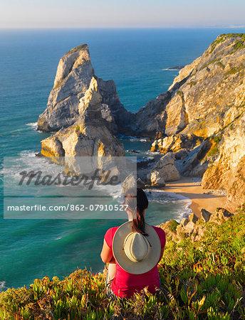 Portugal, Estramadura, Ursa woman sitting on cliff edge (MR)