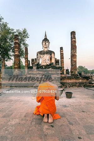 Thailand, Sukhothai Historical Park. Buddhist monk praying at Wat Mahathat temple at sunrise (MR)