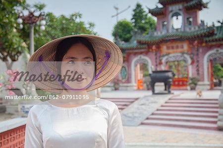 Woman wearing Ao Dai dress at Phouc Kien Assembly Hall, Hoi An (UNESCO World Heritage Site), Quang Ham, Vietnam (MR)
