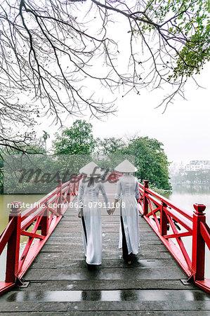 Vietnam, Hanoi, Hoan Kiem lake. Young vietnamese girls in traditional Ao Dai dress walking on Huc bridge (MR)