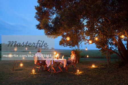 Kenya, Mara North Conservancy. A couple enjoy a romantic dinner overlooking the Mara.