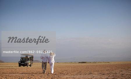 Kenya, Amboseli, Tortilis Camp. A couple walk back to their safari car.