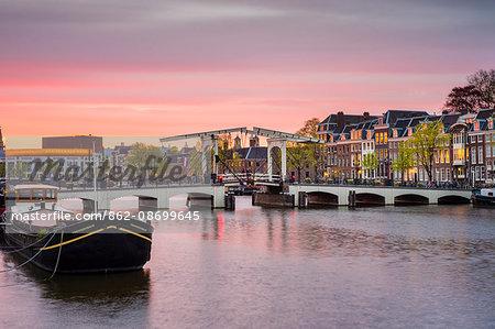 Netherlands, North Holland, Amsterdam. Magere Brug, Skinny Bridge, on the Amstel River at sunset.