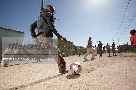 Boy kicking a soccer ball in a dusty street, Vredenburg, Western Cape Province