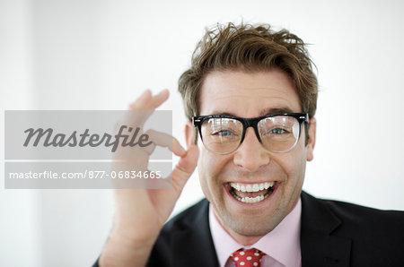 Portrait of smiling businessman doing OK gesture