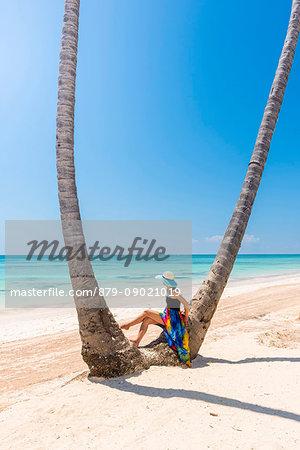 Juanillo Beach (playa Juanillo), Punta Cana, Dominican Republic. Woman under high palm trees on the beach (MR)