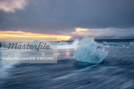 Block of ice on the black beach in Jokulsarlon Glacier Lagoon during a sunset, Eastern Iceland, Europe