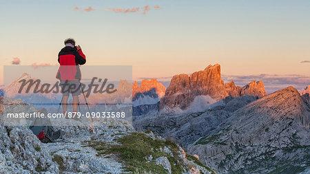 Europe, Italy, Veneto, Belluno, Cortina d Ampezzo. Landscape photographer at sunset on the top of Sass de Stria, Dolomites