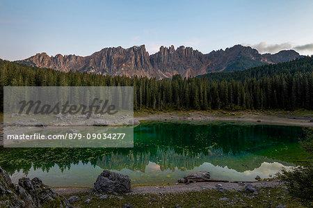 Latemar mountain range and woods are reflected in Lake Carezza at dusk Ega Valley Province of Bolzano South Tyrol Italy Europe