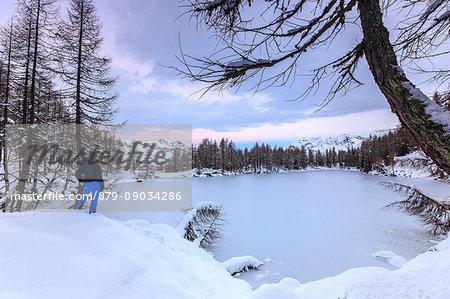 Hiker admires Lago Azzurro completely frozen at dawn Spluga Valley Province of Sondrio Valtellina Lombardy Italy Europe