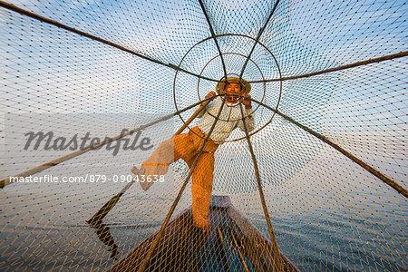 Inle lake, Nyaungshwe, Shan state, Myanmar. Fisherman looking through the fishing net.