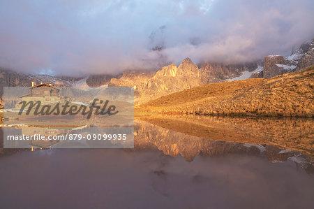 Dolomites Alps, Pale di San Martino reflecting on water with clouds, Baita Segantini, Trentino Alto Adige District, Italy