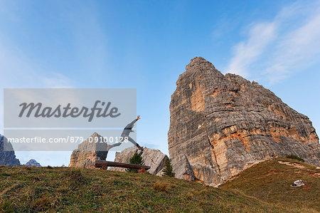 A hiker jumps in fornt of Cinque Torri, Dolomites, Cortina d'Ampezzo, Belluno province, Veneto, Italy