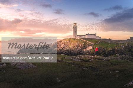 Fanad Head (Fánaid) lighthouse, County Donegal, Ulster region, Ireland, Europe. A photographer on the field at sunrise near Fanad Head lighthouse