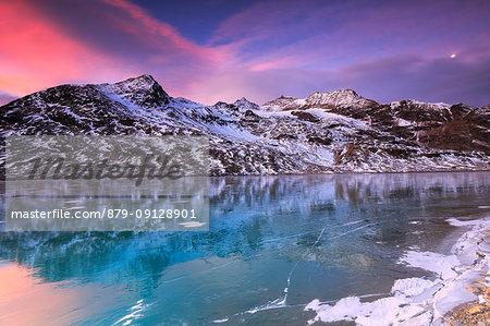 Stunning sunrise on the frozen Lago Bianco(White Lake), Bernina Pass, Engadine, Graubünden, Switzerland.