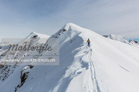 Ski mountaineer on snowy peak, Valgerola, Valtellina, province of Sondrio, Lombardy, Italy