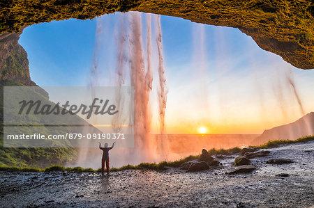 A girl behind the Seljalandsfoss waterfall at sunset (Skogar, Southern Region, Iceland, Europe) (MR)