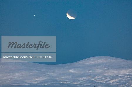 Moon eclipse on the snowy landscape, Troms, Norway