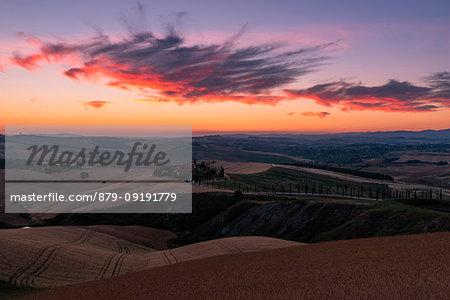 Red clouds over farm house in Tuscany, Asciano, Crete Senesi, Siena province, Tuscany, Italy