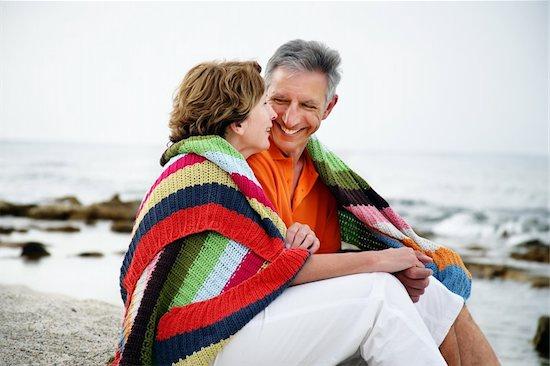 Happy mature couple sitting on the beach. Stock Photo - Royalty-Free, Artist: hannamonika, Image code: 400-04179335
