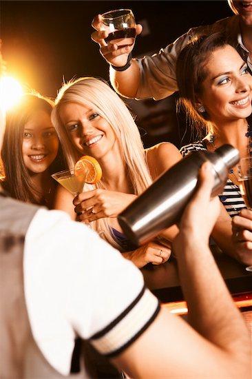 Photo of pretty girls toasting and looking at barman Stock Photo - Royalty-Free, Artist: pressmaster, Image code: 400-04387994