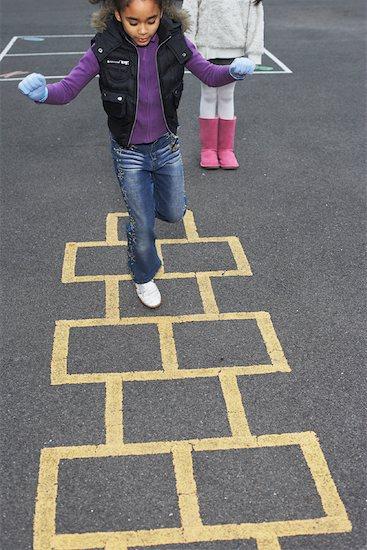 Girl Playing Hopscotch Stock Photo - Premium Royalty-Free, Artist: Masterfile, Image code: 600-01764824