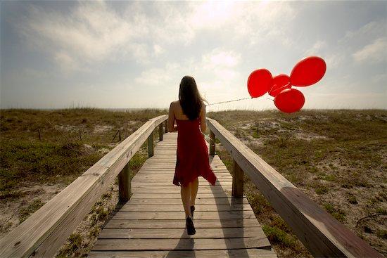 Woman with Balloons Walking along Boardwalk Stock Photo - Premium Royalty-Free, Artist: Kevin Radford, Image code: 600-02081506