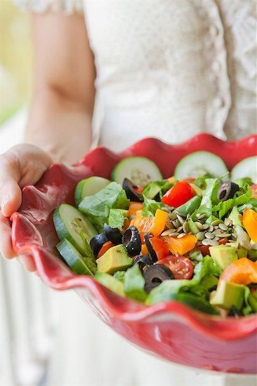 Mid adult woman holding salad bowl Stock Photo - Premium Royalty-Free, Image code: 614-06002185