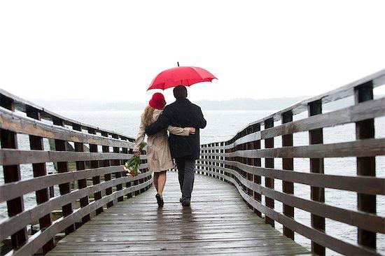 Couple walking on wooden pier in rain Stock Photo - Premium Royalty-Free, Image code: 614-06536903