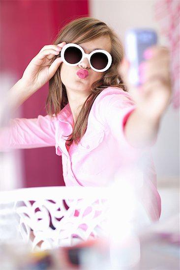 Teenage girl taking picture of herself Stock Photo - Premium Royalty-Free, Image code: 614-06623543