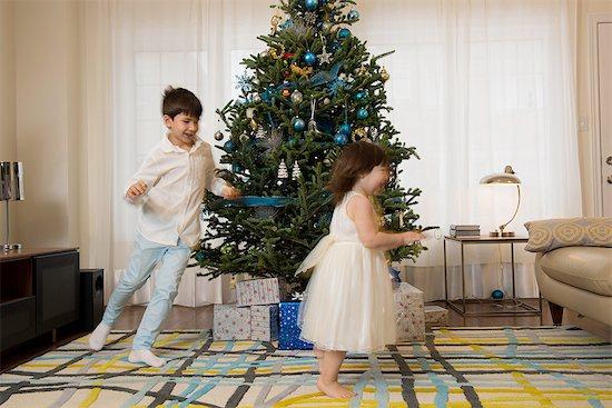 Children playing around Christmas tree Stock Photo - Premium Royalty-Free, Image code: 614-06719323