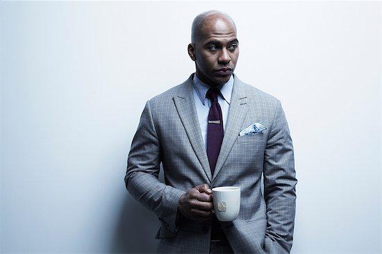 Studio portrait of businessman with mug of tea Stock Photo - Premium Royalty-Free, Image code: 614-06897221
