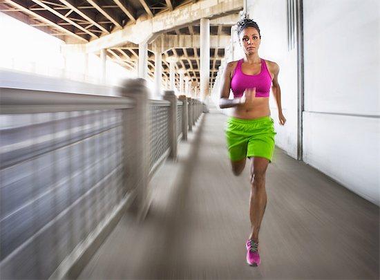 Blurred shot of young woman running on urban bridge Stock Photo - Premium Royalty-Free, Image code: 614-07453278