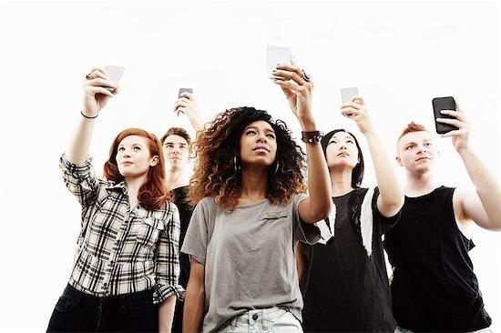 Studio portrait of five young adults taking selfies on smartphones Stock Photo - Premium Royalty-Free, Image code: 614-07735557