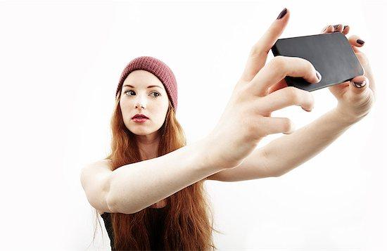 Studio portrait of young woman making selfie on smartphone Stock Photo - Premium Royalty-Free, Image code: 614-07768180