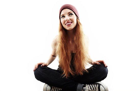 Studio portrait of young woman sitting cross legged on floor Stock Photo - Premium Royalty-Free, Image code: 614-07768182