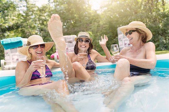 Three mature women sitting in paddling pool, drinking wine Stock Photo - Premium Royalty-Free, Image code: 614-07806346
