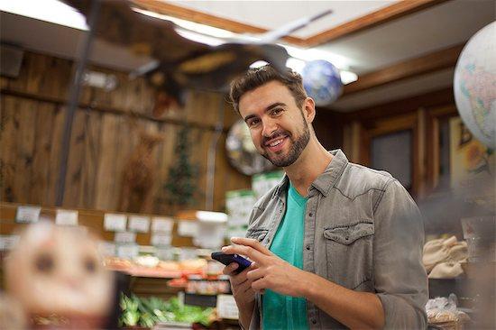 Man using smartphone in health food store Stock Photo - Premium Royalty-Free, Image code: 614-08030992
