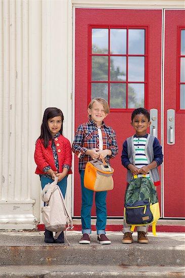 Portrait of elementary schoolgirl and boys holding satchels at elementary school doorway Stock Photo - Premium Royalty-Free, Image code: 614-08535720