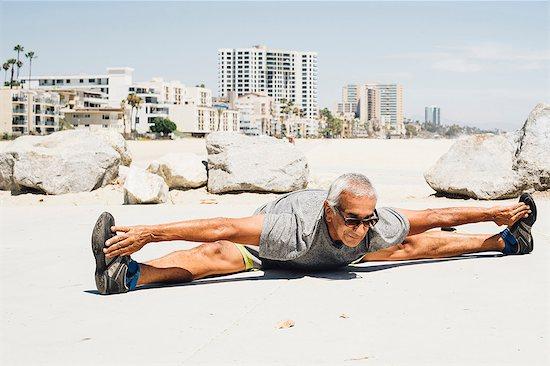 Senior man, exercising on beach, stretching, Long Beach, California, USA Stock Photo - Premium Royalty-Free, Image code: 614-08726425